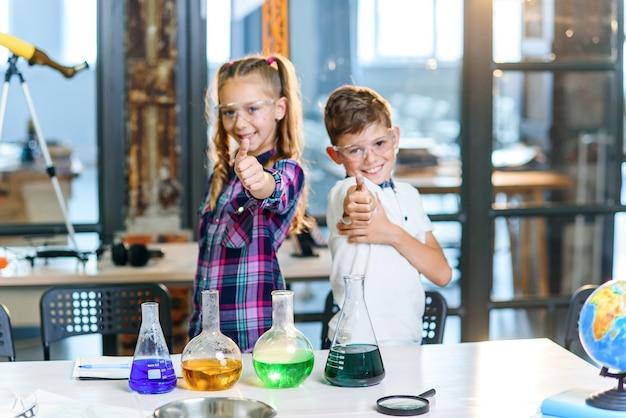 Il ritratto ha sparato di due bambini caucasici allegri dello scienziato in occhiali di protezione che mostrano i pollici su nella classe chimica della scuola primaria