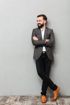 Il ritratto integrale del giovane in rivestimento che posa sulla macchina fotografica con l'ampio sorriso e le mani ha attraversato, isolato sopra grey