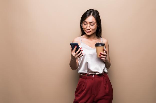 Il ritratto integrale della donna asiatica sorridente che per mezzo del telefono cellulare mentre tiene la tazza di caffè per andare ha isolato sopra la parete beige