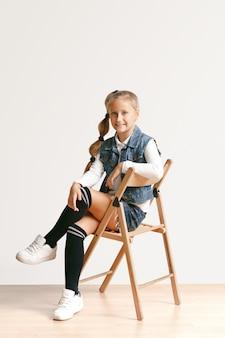Il ritratto integrale di piccola ragazza teenager sveglia in jeans alla moda copre l'esame della macchina fotografica