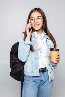Il ritratto laterale di giovane donna dello studente parla con smartphone, tenendo il caffè per andare tazza isolata sulla parete grigia