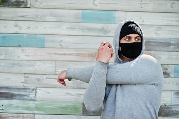 Il ritratto mette in mostra l'uomo arabo in maschera e felpa con cappuccio mediche nere durante la quarantena del coronavirus.