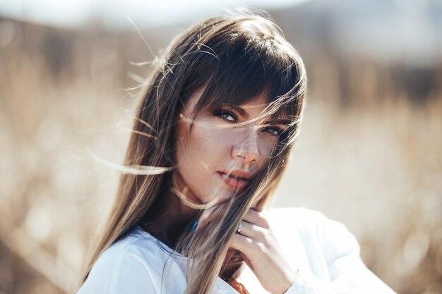 Il ritratto si chiude su di giovane bella donna, sulla molla ha offuscato la natura. ragazza dai capelli biondi con look sexy, retroilluminazione solare