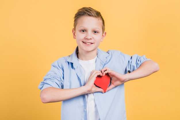 Il ritratto sorridente di un ragazzo che mostra il cuore rosso modella la condizione contro il contesto giallo