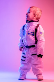 Il ritratto variopinto di un ragazzino che indossa l'astronauta americano copre, illuminato con luce rossa e blu. concetto di astronauta e bambini.