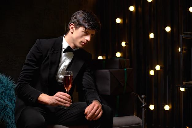 Il riuscito uomo bello in vestito classico tiene un bicchiere di champagne. buon natale e felice anno nuovo 2020
