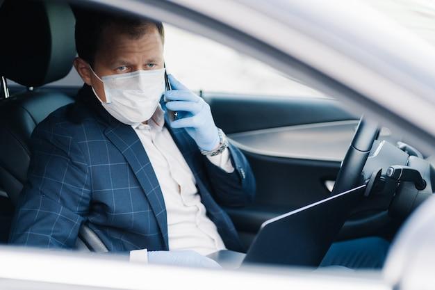 Il riuscito uomo d'affari aspetta qualcuno in automobile, mette la maschera medica durante l'epidemia come protezione dal virus, ha i colloqui telefonici, usa il computer portatile moderno. covid-19, quarantena, infezione, concetto di malattia