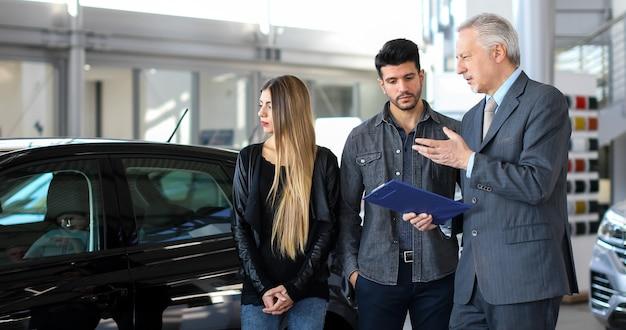 Il rivenditore di auto esalta le caratteristiche di un'auto per una coppia leggendo un documento