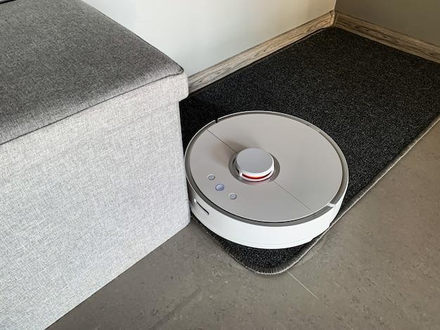 Il robot aspirapolvere funziona a pavimento in un salotto.