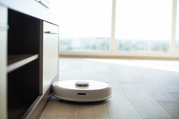 Il robot aspirapolvere funziona sul pavimento di legno in un salotto
