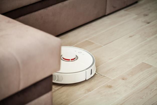 Il robot aspirapolvere funziona sul pavimento di legno in un salotto,