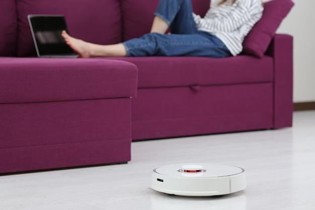 Il robot aspirapolvere pulisce. ragazza che riposa a casa sul divano, mentre l'aspirapolvere robot. concetto di tempo per te stesso. casa intelligente. la ragazza moderna ottimizza il suo tempo. concetto di robot. messa a fuoco selettiva