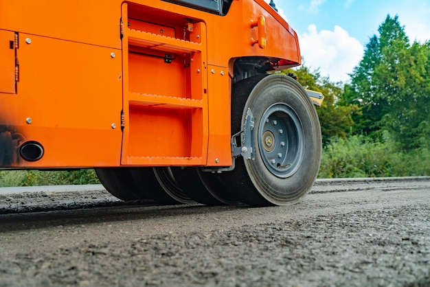 Il rullo stradale arancione rende la pavimentazione.