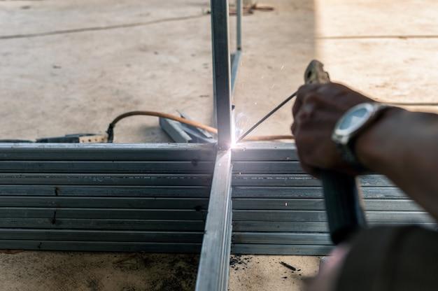 Il saldatore industriale sta saldando il tubo d'acciaio