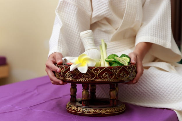 Il sale asiatico della tenuta della donna sfrega per il massaggio alla stazione termale.