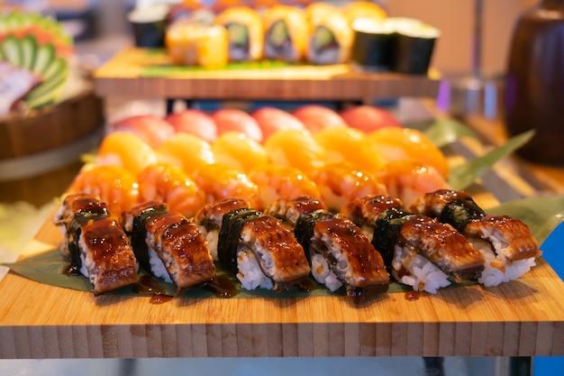 Il salmone arrostito arriva a fiumi l'insieme dei sushi, concetto del fondo