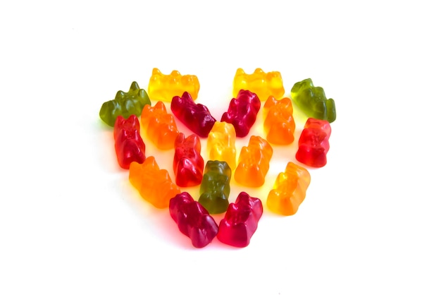 Il sapore gommoso della frutta del preparato della caramella di forma dell'orso di gelatina nella vista laterale di stile di forma del cuore isolato su fondo bianco