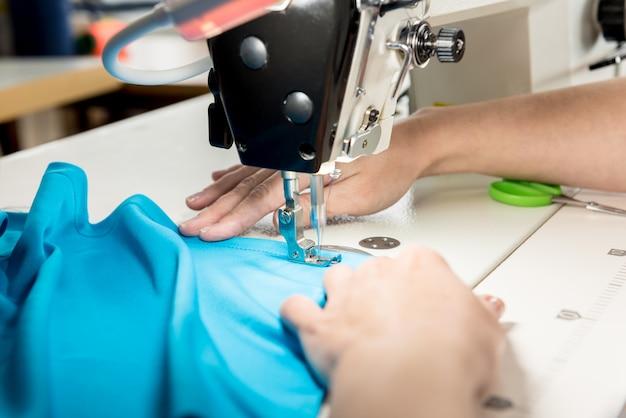 Il sarto del progettista cuce il vestito. la donna usa la macchina da cucire per il suo lavoro. panno di lavorazione sartoriale. fabbrica tessile.
