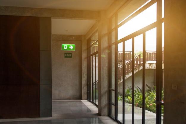 Il segnale di uscita di emergenza verde ed etichetta nessun fumo nell'angolo di sosta che mostra la via di fuga e avvisa la consapevolezza della sicurezza