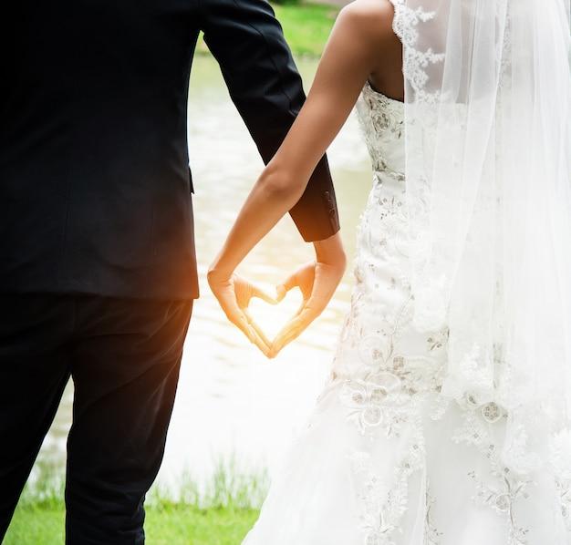 Il segno della mano dell'amore fatto da sposo e sposa