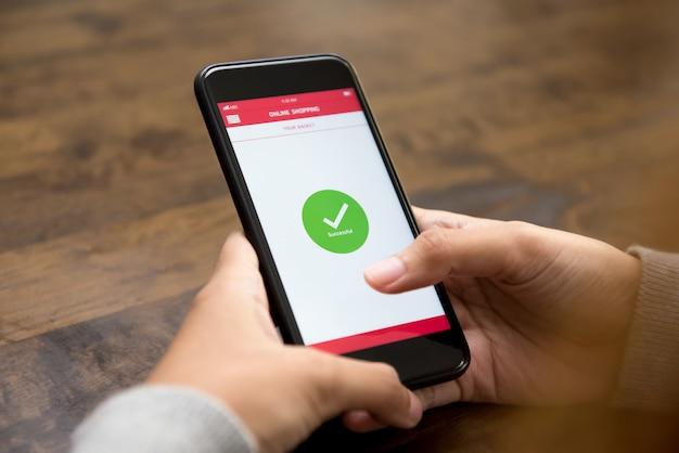 Il segno di conferma dello shopping online riuscito appare sullo schermo dello smartphone dopo il pagamento