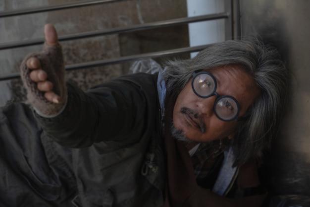 Il senzatetto è sdraiato sulla passerella in città. sta alzando la mano per dare aiuto.