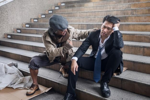 Il senzatetto incoraggia il triste uomo d'affari