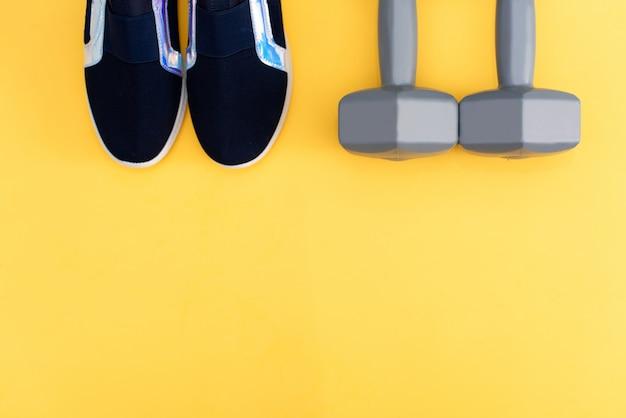 Il set dell'atleta con vestiti femminili, manubri e bottiglia d'acqua sul giallo