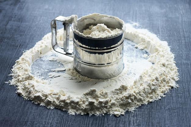 Il setaccio della tazza è riempito di farina, la farina è sparsa intorno su fondo di legno scuro.