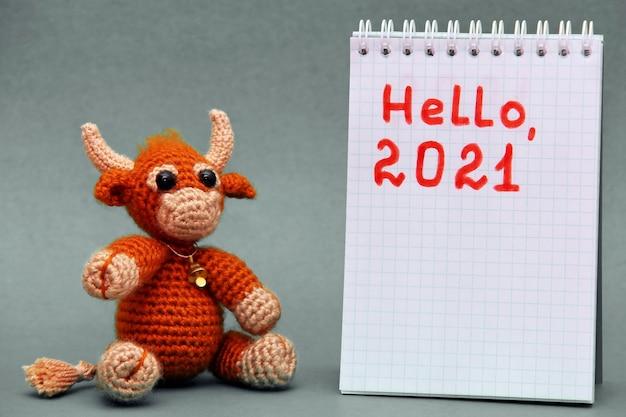 Il simbolo del nuovo anno 2021. il toro giocattolo su uno sfondo grigio. felice anno nuovo.