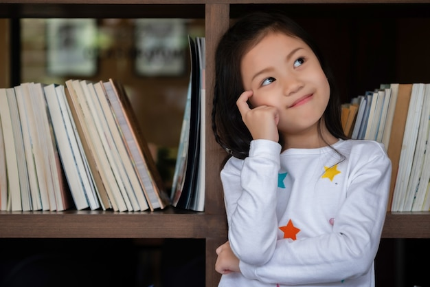 Il sitdown sveglio della ragazza ha sorriso e cerca nella stanza, concetto dei bambini, concetto di istruzione