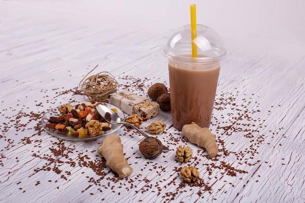 Il smoothie marrone sano con la noce e la frutta candita si trovano sul tavolo