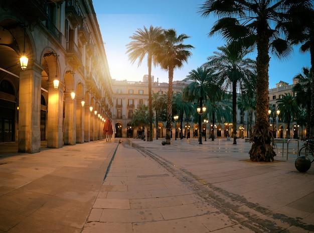 Il sole sorge sopra la plaza real illuminata nel quartiere gotico di barcellona, in spagna