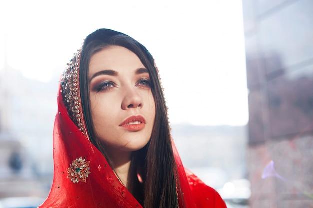 Il sole splende sulla bella sposa indù nel sari rosso