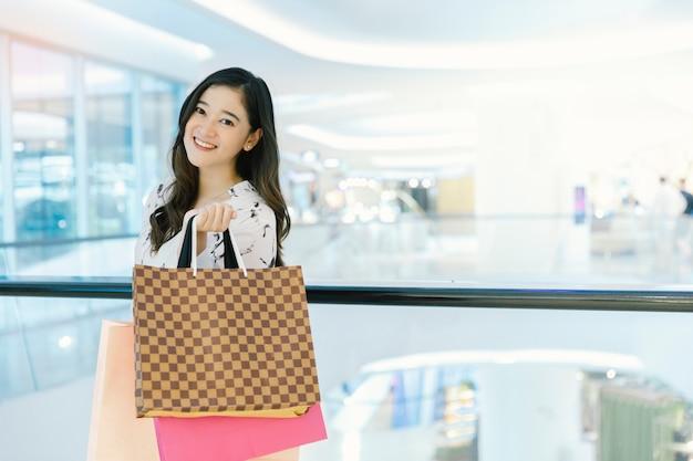 Il sorriso asiatico della donna con i sacchetti della spesa gode nel centro commerciale