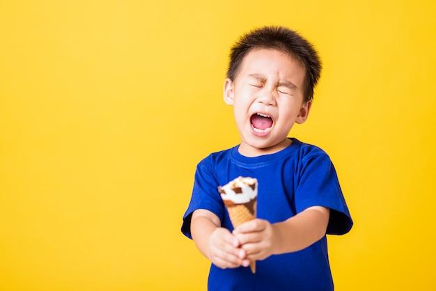 Il sorriso asiatico felice del ragazzino del bambino tiene il cono della cialda del gelato al cioccolato zuccherato