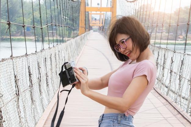 Il sorriso felice del giovane viaggiatore asiatico della donna prende il selfie sul ponte