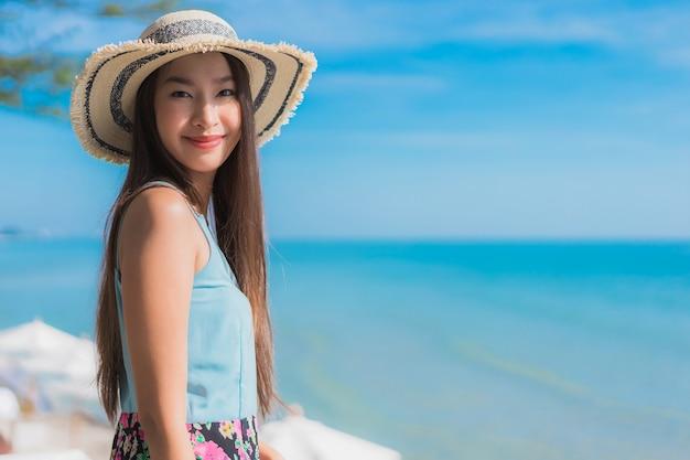Il sorriso felice della bella giovane donna asiatica del ritratto si rilassa intorno all'oceano ed al mare della spiaggia