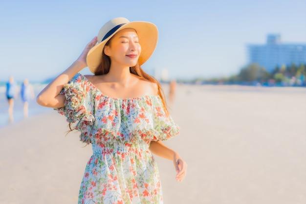 Il sorriso felice della bella giovane donna asiatica del ritratto si rilassa intorno all'oceano tropicale del mare della spiaggia
