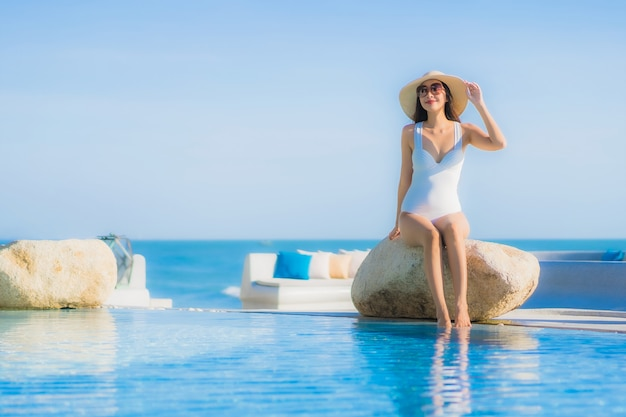 Il sorriso felice della bella giovane donna asiatica del ritratto si rilassa intorno alla piscina all'aperto nella località di soggiorno dell'hotel