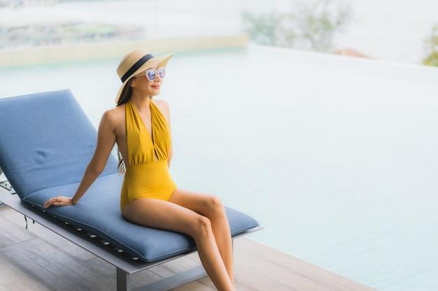 Il sorriso felice della bella giovane donna asiatica del ritratto si rilassa intorno alla piscina all'aperto nella vacanza di festa