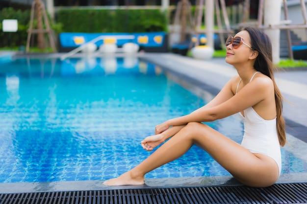 Il sorriso felice della bella giovane donna asiatica del ritratto si rilassa intorno alla piscina all'aperto