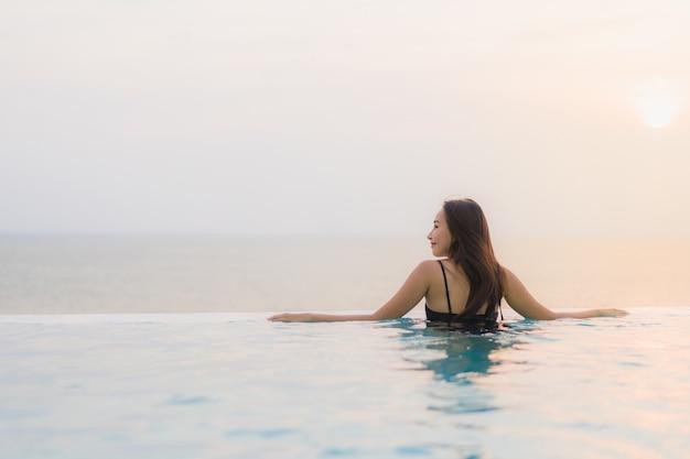 Il sorriso felice della bella giovane donna asiatica del ritratto si rilassa intorno alla piscina nella località di soggiorno dell'hotel