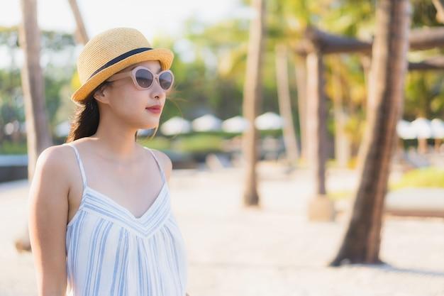 Il sorriso felice della bella giovane donna asiatica del ritratto si rilassa intorno alla spiaggia ed al mare vicini