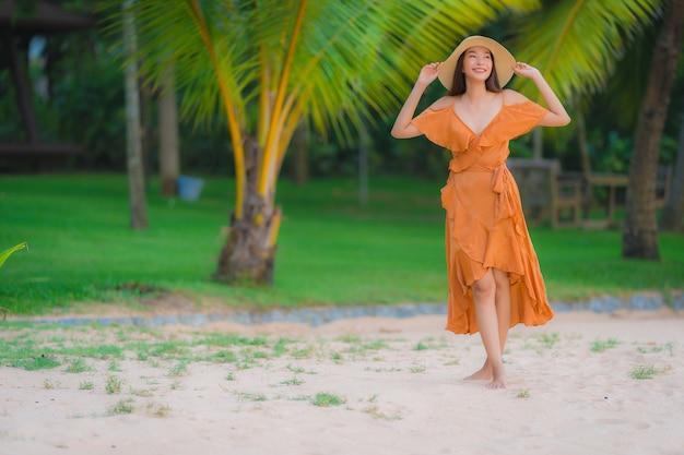 Il sorriso felice della bella giovane donna asiatica del ritratto si rilassa sull'oceano del mare della spiaggia