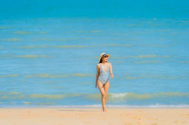 Il sorriso felice della bella giovane donna asiatica del ritratto si rilassa sull'oceano tropicale del mare della spiaggia per il viaggio di svago