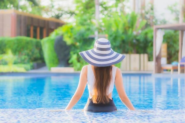 Il sorriso felice della giovane donna asiatica del bello ritratto si rilassa intorno alla piscina nell'hotel di località di soggiorno
