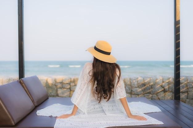 Il sorriso felice della giovane donna asiatica del ritratto si rilassa intorno all'oceano del mare della spiaggia