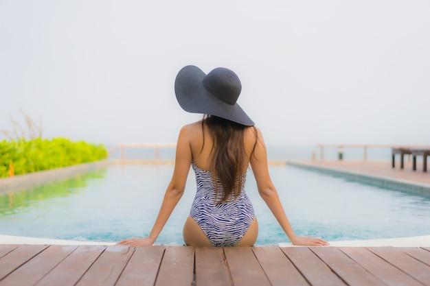 Il sorriso felice della giovane donna asiatica del ritratto si rilassa intorno alla piscina all'aperto