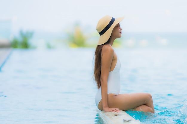 Il sorriso felice della giovane donna asiatica del ritratto si rilassa intorno alla piscina nella località di soggiorno dell'hotel